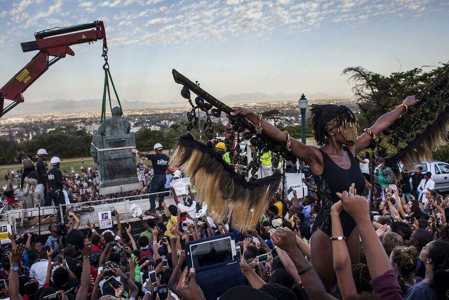 "Students cheer as the Cecil Rhodes statue is being removed from the University of Cape Town on April 9, 2015 in Cape Town, South Africa. The statue of British colonialist Cecil John Rhodes was removed from the University of Cape Town as a result of a month long protest by students citing the statue ""great symbolic power"" which glorified someone ""who exploited black labour and stole land from indigenous people"".  Photo: Charlie Shoemaker"