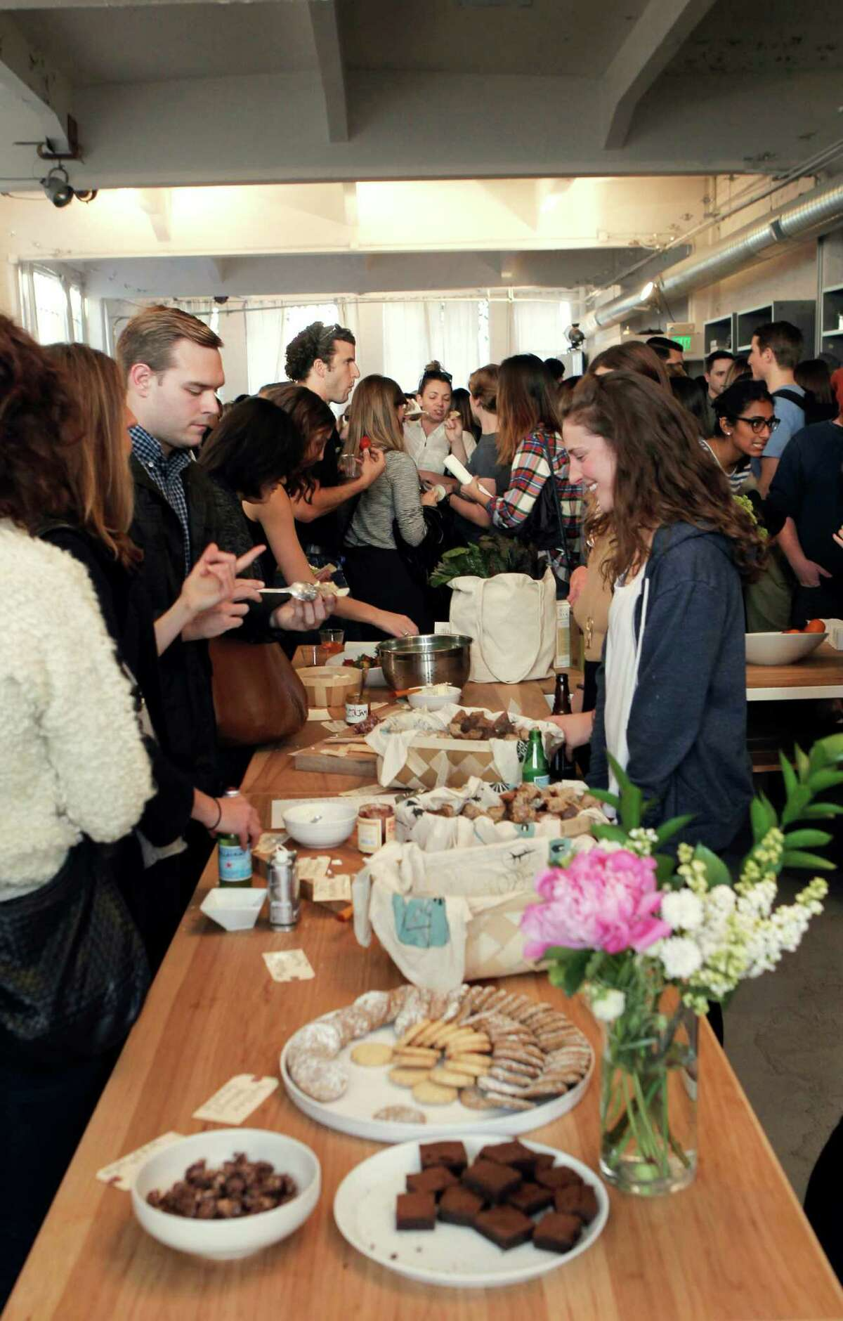 Customers socialize and sample Good Eggs snacks at the monthly open studio event at Everlane's office.