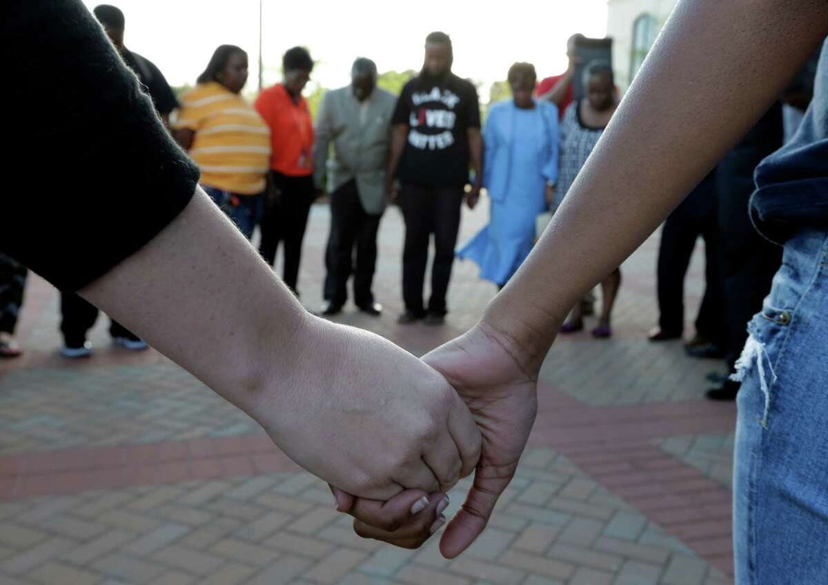 People hold hands in prayer during a rally for the killing of Walter Scott by a North Charleston police officer Saturday, after a traffic stop in North Charleston, S.C., Thursday, April 9, 2015. The officer, Michael Thomas Slager, has been fired and charged with murder.