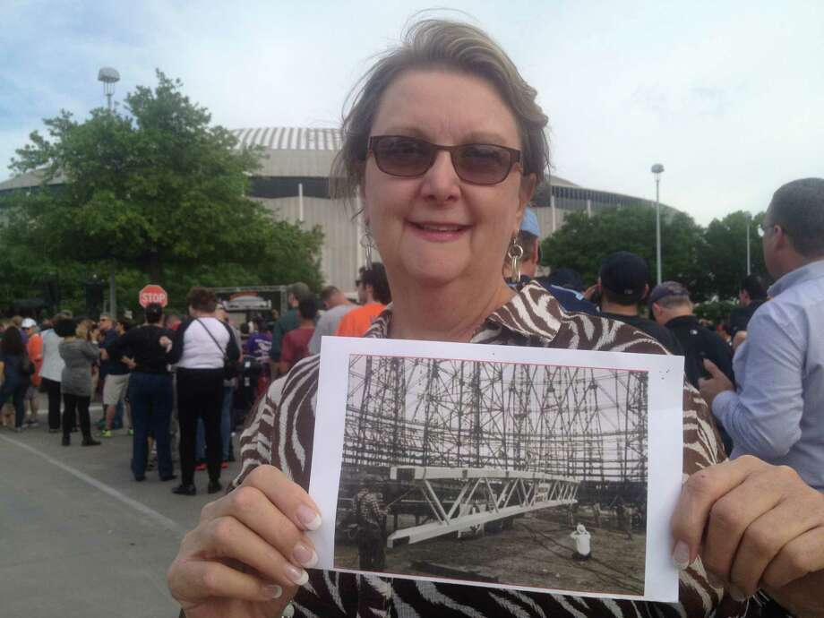 Connie Crabb Douglas holds a photo of her father building the Astrodome in 1963. He was an iron worker with the 84th Iron Workers' Union in Houston, and considered working on the dome among his greatest achievements. Photo: Dylan Baddour