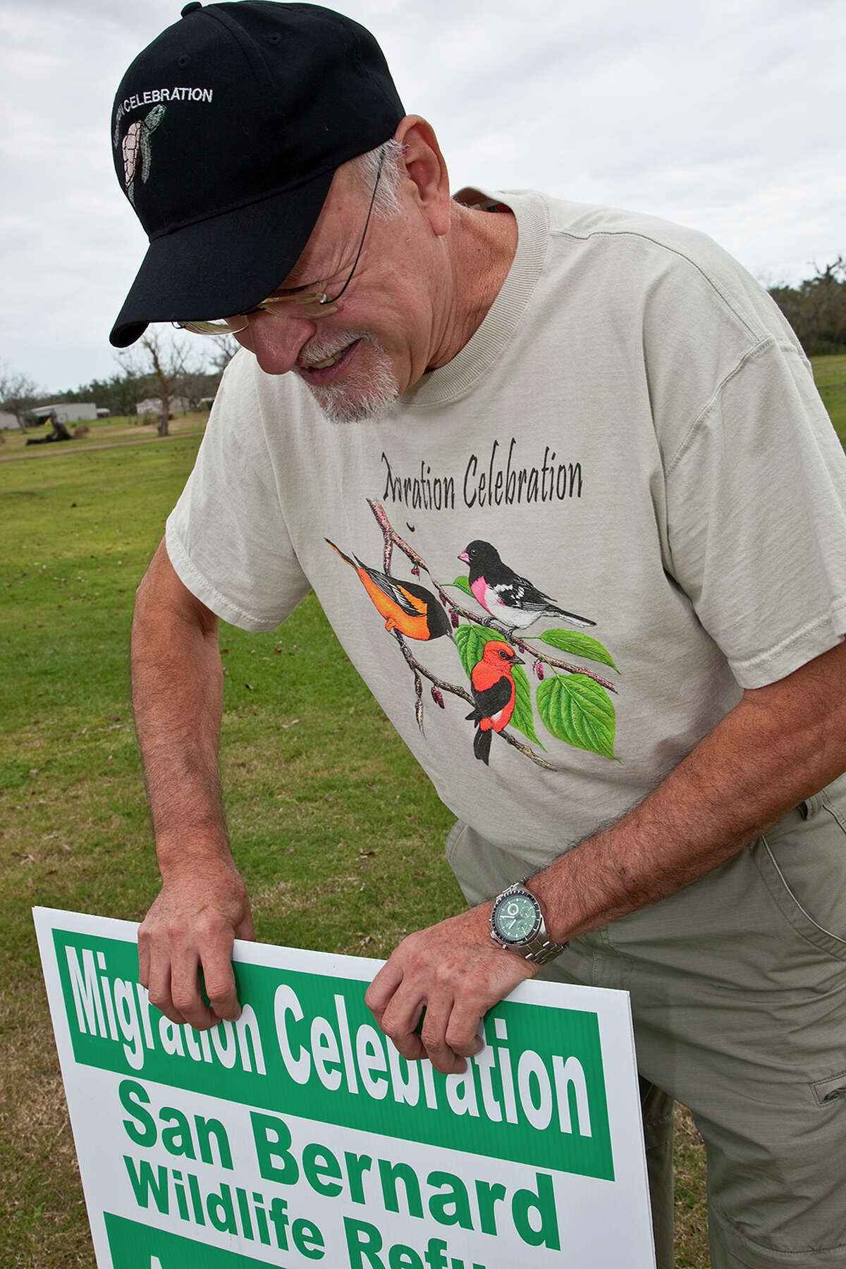 Ed Barrios, a Migration Celebration volunteer, installs a yard signing announcing the event.