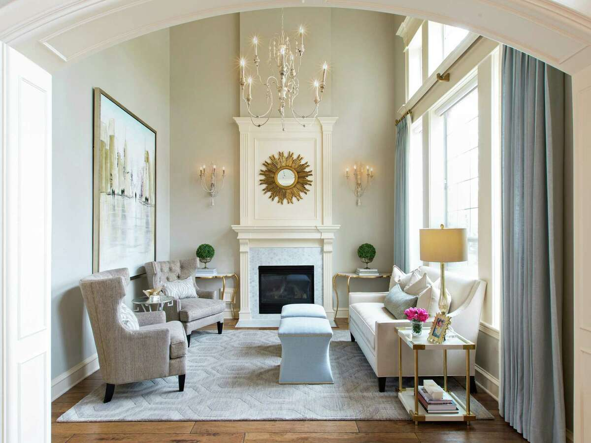 A light color palette and a lightweight chandelier open up the small living room, making it seem bigger and brighter.