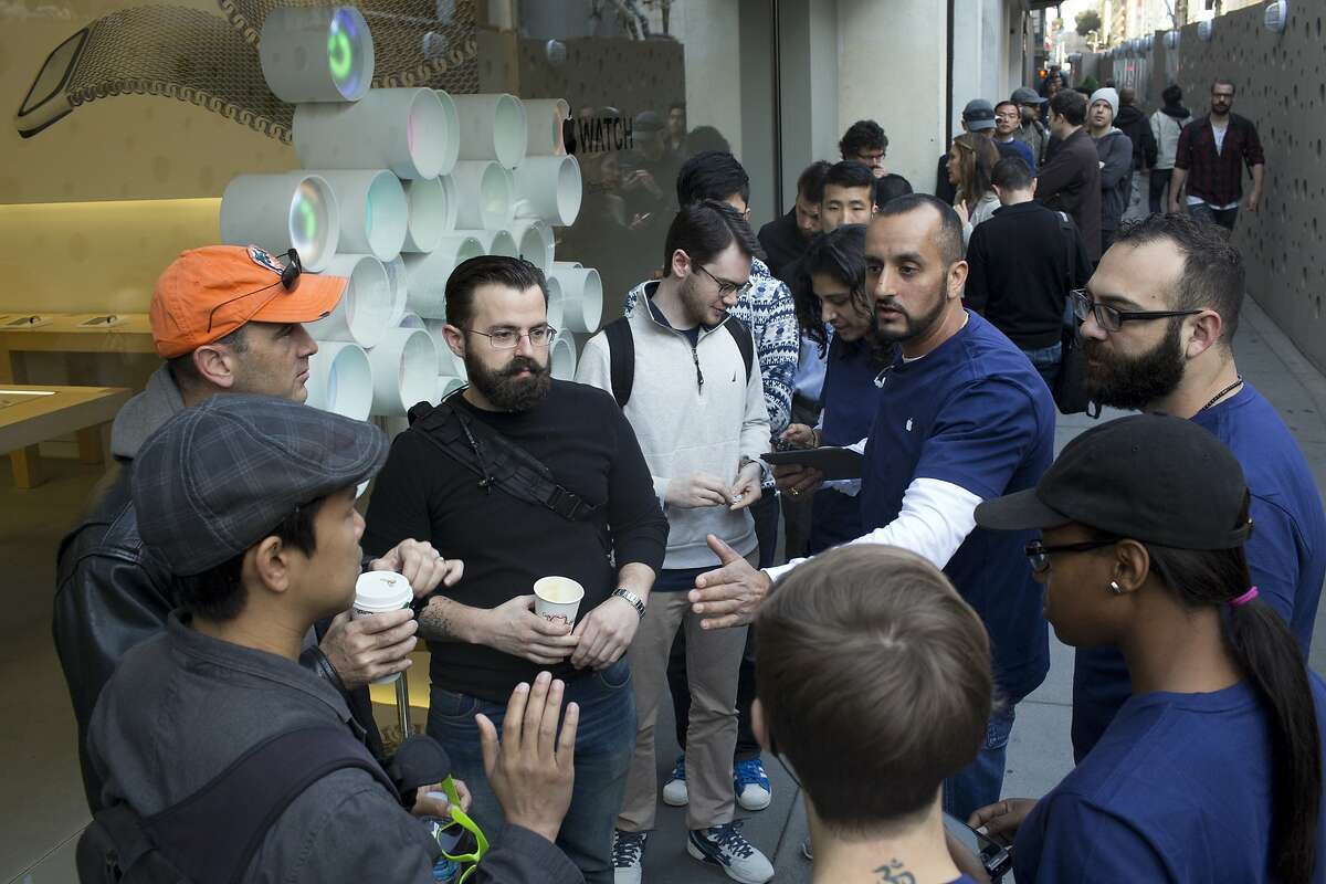 Apple employees talk to customers lining up at the Apple Store to try on the Apple Watch in San Francisco, Calif. on Friday, April 10, 2015.