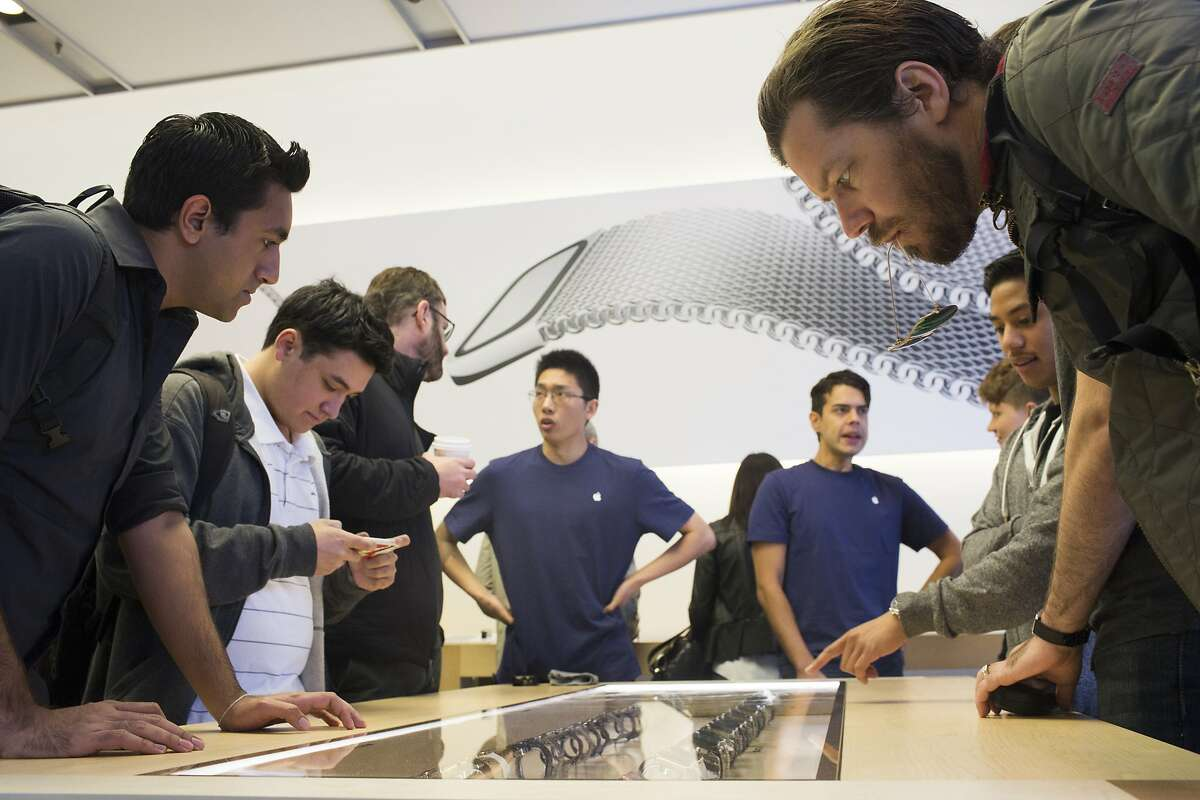 Sam Hickmann (right) of San Francisco, looks at a display case of Apple Watches at the Apple Store in San Francisco in 2015.