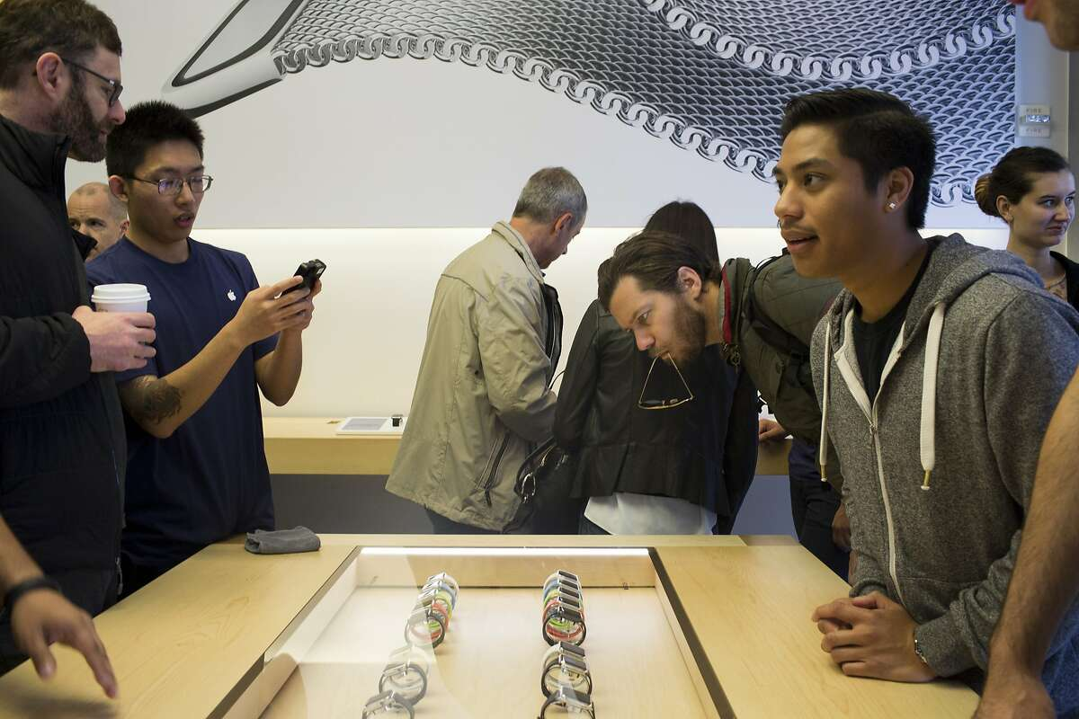 People look at a case displaying the Apple Watch at the Apple Store in San Francisco, Calif. on Friday, April 10, 2015.