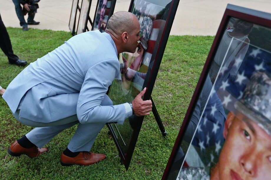 Juan Velez kisses a portrait of his daughter, PFC Francheska Velez before the Fort Hood Purple Heart and Defense of Freedom Medal Ceremony, Friday, April 10, 2015. The U.S. Army awarded Purple Hearts and the Defense of Freedom Medal to soldiers and civilians who were wounded or killed in the Nov. 5, 2009 massacre that left 13, dozen of them soldiers, dead and 31 injured. The attacker, Maj. Nidal Hasan, was convicted on August 2013. Photo: JERRY LARA, San Antonio Express-News / © 2015 San Antonio Express-News
