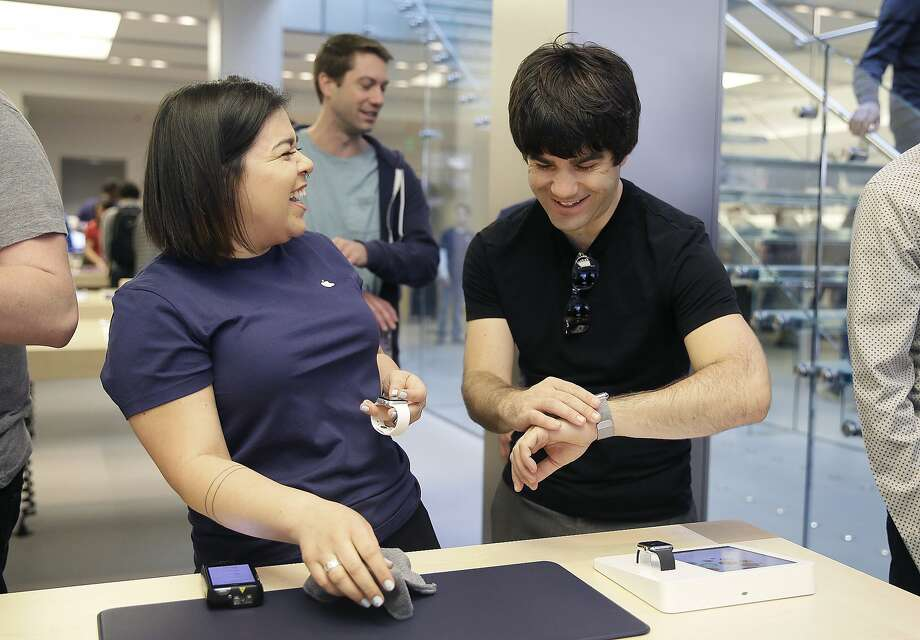 An Apple employee, left, laughs next to a customer trying on Apple's new watch, in San Francisco, Friday, April 10, 2015.  Photo: Eric Risberg, Associated Press