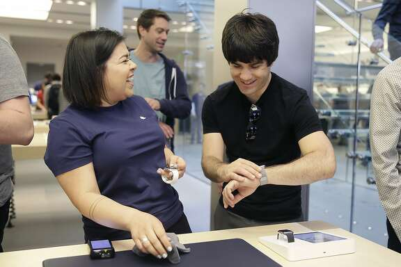 An Apple employee, left, laughs next to a customer trying on Apple's new watch, in San Francisco, Friday, April 10, 2015. Apple has started taking orders for the watch on its website and the Apple Store app. Currently, that's the only way Apple is selling the watch, with shipments scheduled to start April 24. (AP Photo/Eric Risberg)
