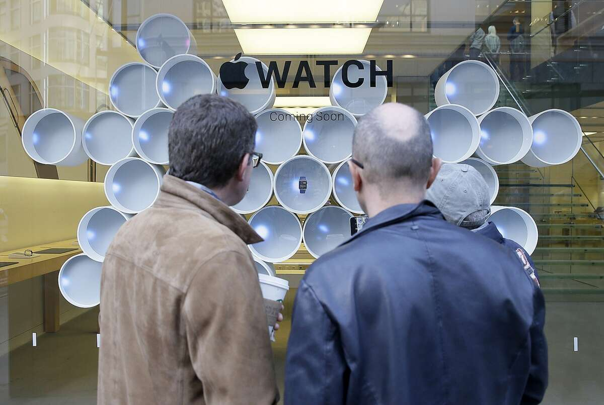 Customers wait in line outside of an Apple store in front of a display for Apple's new watch in San Francisco, Friday, April 10, 2015. Apple has started taking orders for the watch on its website and the Apple Store app. Currently, that's the only way Apple is selling the watch, with shipments scheduled to start April 24. (AP Photo/Eric Risberg)