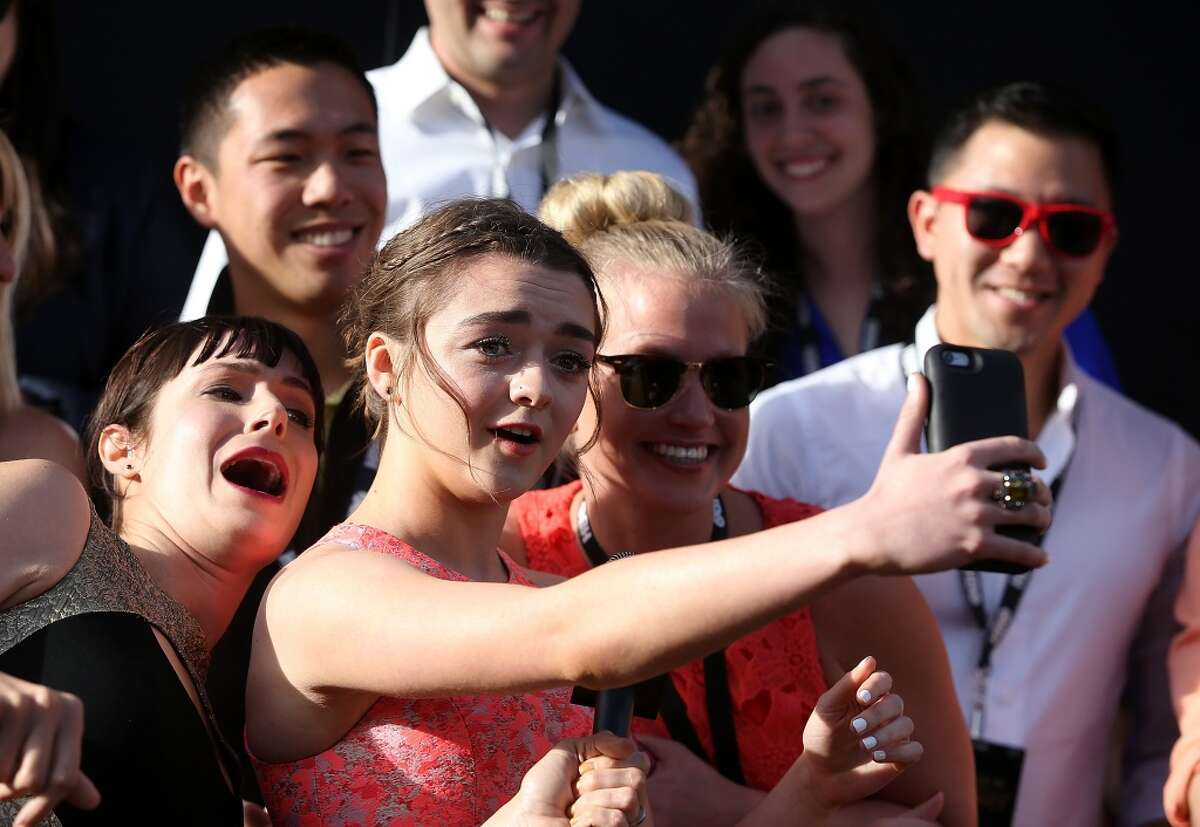 Actress Maisie Williams (C) does a selfie with fans as she attends the premiere of HBO's 'Game of Thrones' Season 5 at San Francisco Opera House on March 23, 2015 in San Francisco, California.