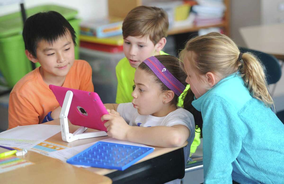 Fourth-graders, from left, Ibuki Matsushita, Will Duncan, Tori Ware and Logan Gilbrid use an iPad for a math project at North Mianus School in Greenwich, Conn. Wednesday, April 1, 2015. With the advances of technology in the classroom, students and teachers are balancing digital learning on platforms like the iPad with traditional pen and paper, non-digital resources.