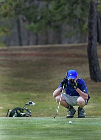 Colin Buyck, 15, of Guilderland lines up a shot on the 18th green on opening day at Stadium Golf Course Friday, April 10, 2015, in Schenectady, N.Y.    (Skip Dickstein/Times Union) Photo: SKIP DICKSTEIN / 00031381A