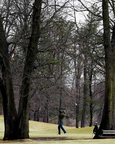 A golfer is framed by leafless trees as he drives the ball on opening day at Stadium Golf Course Friday, April 10, 2015, in Schenectady, N.Y.    (Skip Dickstein/Times Union) Photo: SKIP DICKSTEIN / 00031381A