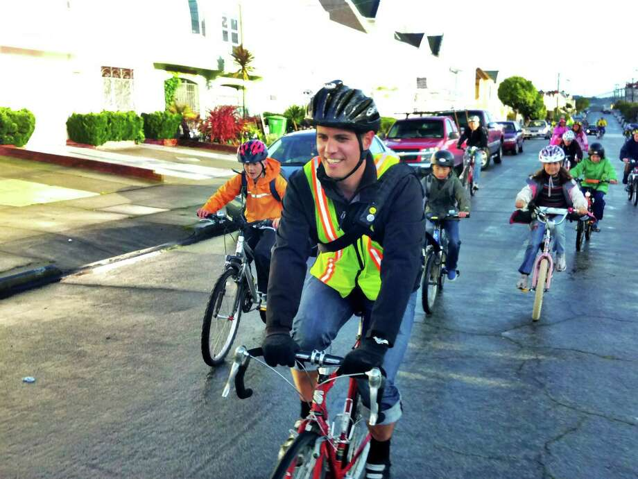 """A biking chaperone leads a """"bike train"""" to Sunnyside Elementary during Bike & Roll to School Week. Bike trains are groups of students and guardians who ride to school together. Photo: San Francisco Bicycle Coalition / ONLINE_YES"""