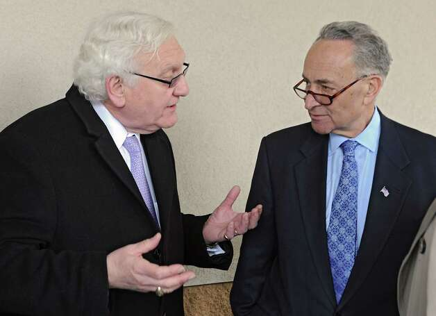 Johnstown Mayor Michael Julius, left, talks to U.S. Senator Charles Schumer after the senator urged the Federal Emergency Management Agency (FEMA) to examine the outdated flood maps that have incorrectly placed the Johnstown Shopping Center, as well as up to 50 other properties in the surrounding area, in the Cayudutta Creek's flood zone on Friday, April 10, 2015 in Johnstown, N.Y. (Lori Van Buren / Times Union) Photo: Lori Van Buren / 00031385A