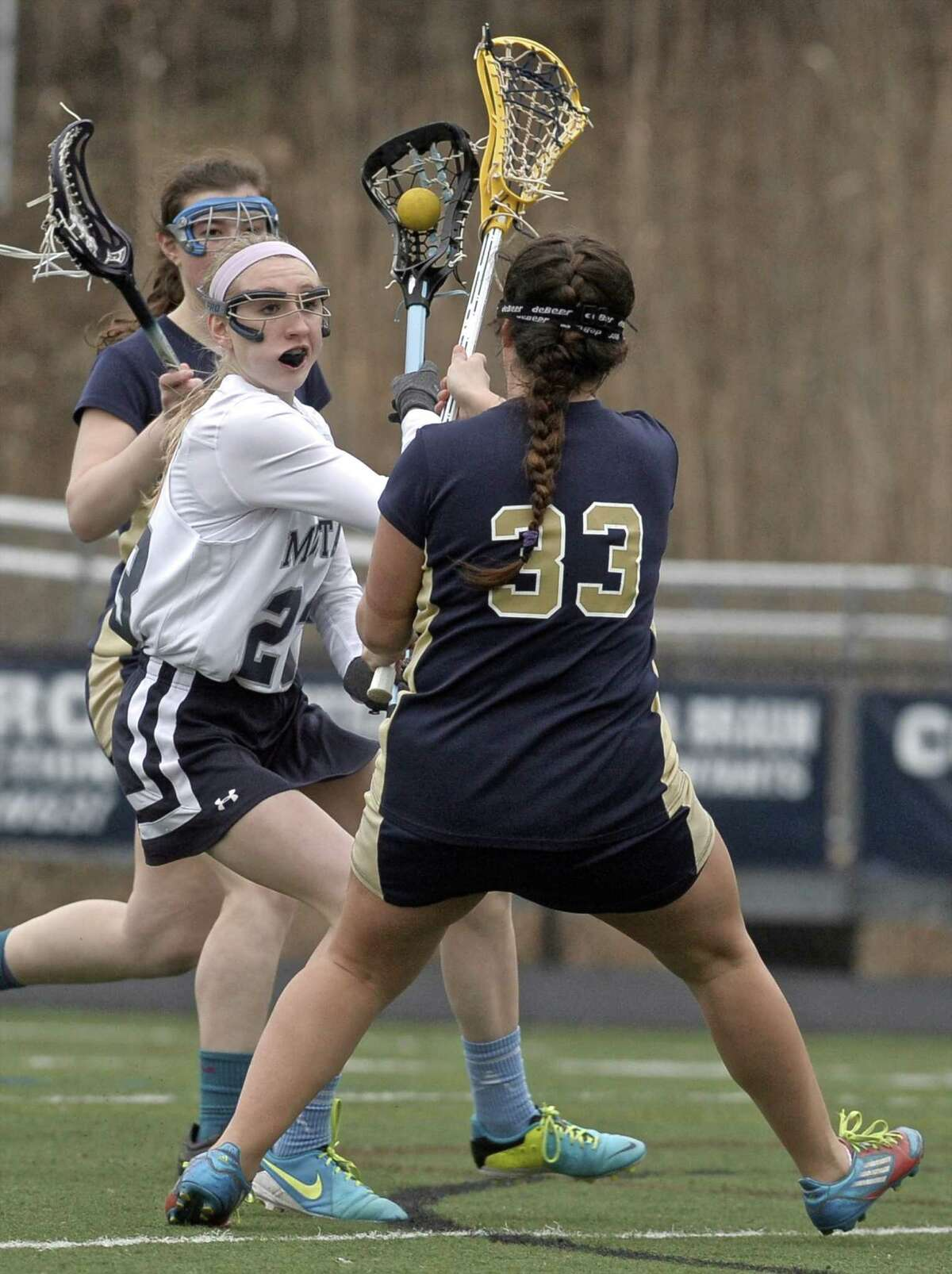 Immaculate's Caroline Wax (23) is caught between Notre Dame's Alicia Berard (33) and Alex D'Aurio during the girls high school lacrosse game between Notre Dame-Fairfield and Immaculate high schools, on Friday afternoon, April 10, 2015, played at Immaculate High School, in Danbury, Conn.