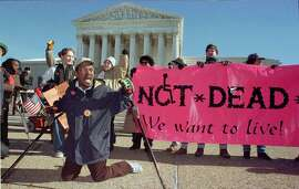 """WAS05:COURT-SUICIDE:WASHINGTON,8JAN97 - Gregory Dugan of Washington D.C. (L) leads a group of protestors against doctor-assisted suicide in front of the U.S. Supreme Court January 8, while inside the high court heard arguments on both sides of the right-to-die issue. Several justices expressed reservations about overturning existing state bans on doctor-assisted suicide. The full sign in the background reads """"We're Not Dead Yet."""" cm/Photo by Mike Theiler     REUTERS"""