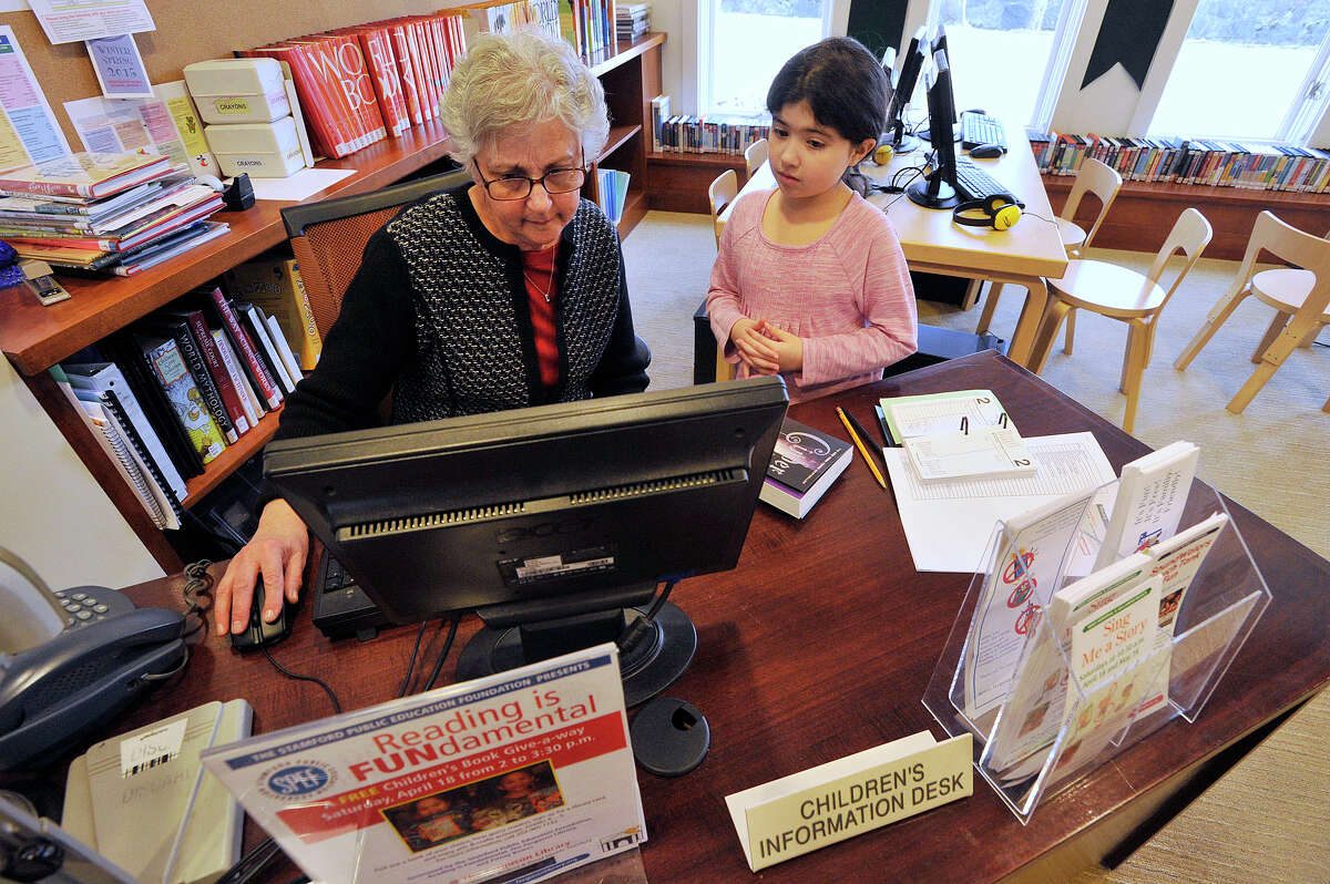 Youth services librarian Shelley Taylor helps nine-year-old Kristina DeLelle find a book at the Children's Information Desk at the Weed Memorial and Hollander Branch Library in the Springdale neighborhood of Stamford, Conn., on Thursday, April 2, 2015.