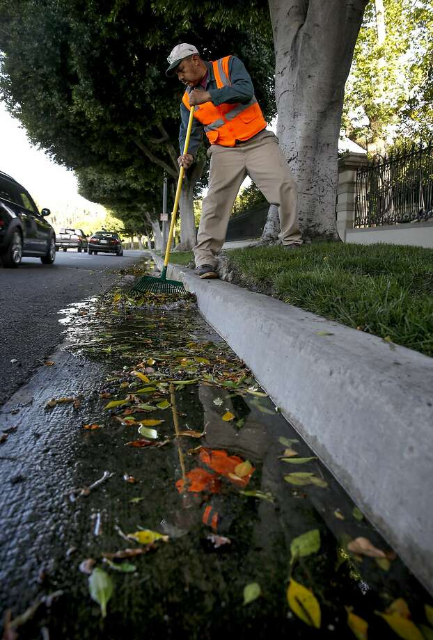 Gardener, Valentine Lopez  collects debris from runoff water which puddled in the gutters along Sunset Blvd. after early morning irrigation in the Southern California City of Beverly Hills, Calif., as seen on Thurs. April 9, 2015. The city of Beverly Hills one the the largest users of water in California may be required to cut their water consumption by 35 percent during this the fourth year of drought in the State of California. Photo: Michael Macor, The Chronicle