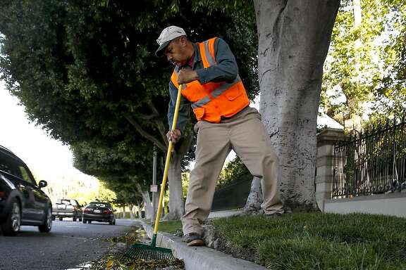 Gardener, Valentine Lopez  collects debris from runoff water which puddled in the gutters along Sunset Blvd. after early morning irrigation in the Southern California City of Beverly Hills, Calif., as seen on Thurs. April 9, 2015. The city of Beverly Hills one the the largest users of water in California may be required to cut their water consumption by 35 percent during this the fourth year of drought in the State of California.