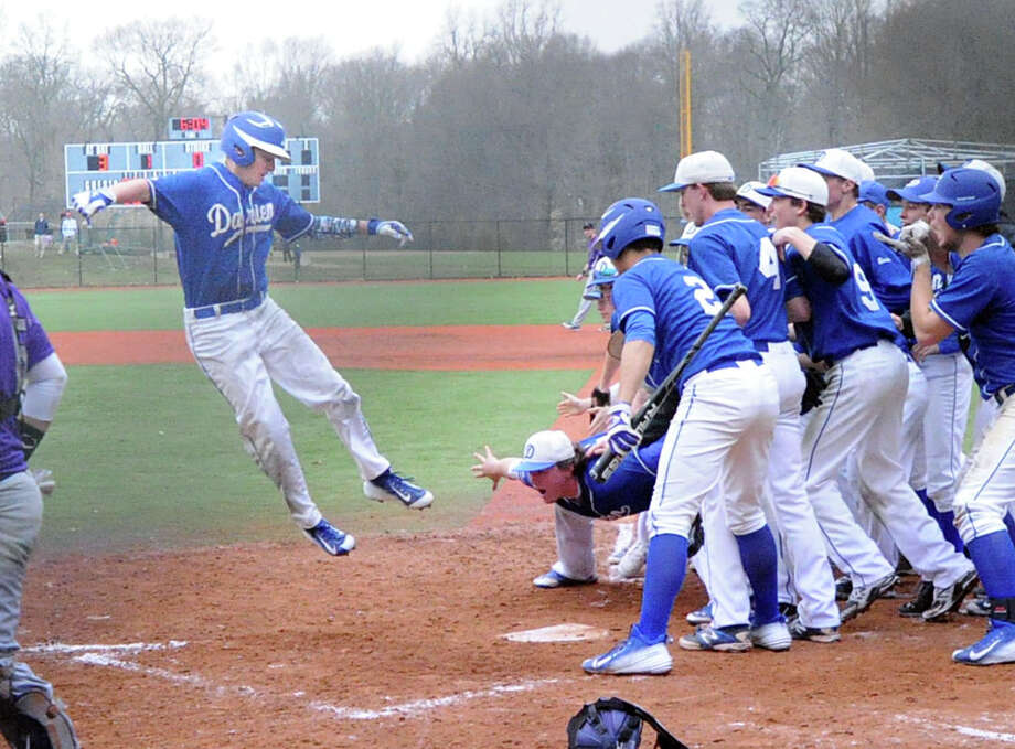 At left, Darien's Jake Frasca jumps high in the air before touching home plate after hitting a solo home run in the top of the 7th inning in the high school baseball game that turned out to be the winning run in the game between Darien High School and Westhill High School at Darien, Conn., Friday, April 10, 2015. Darien won the game 5-4. Photo: Bob Luckey / Greenwich Time