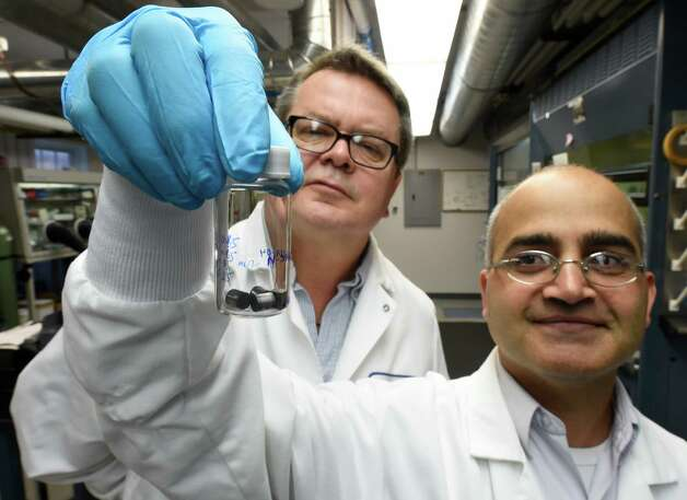 Manufacturing chemist Gregg Bosak, left, and Bed Poudel, CTO of Evident Technologies, check a bottle of thermoelectric elements at the Evident Technologies Wednesday morning, April 9, 2015, in Troy, N.Y.  (Skip Dickstein/Times Union) Photo: SKIP DICKSTEIN / 00031364A
