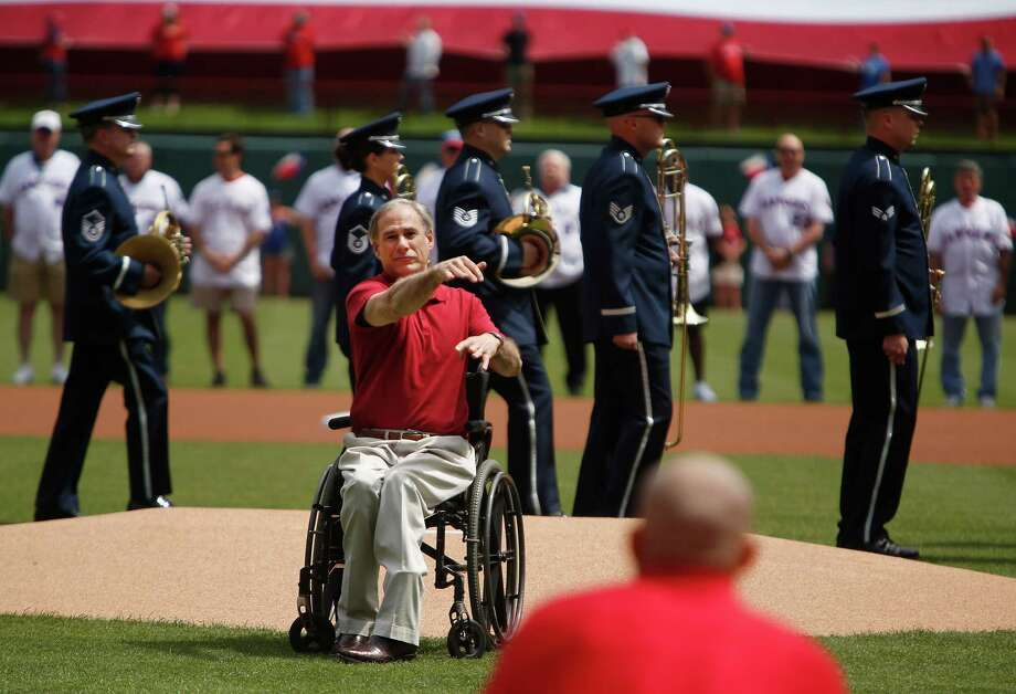 "Texas Gov. Greg Abbott throws a ""Texas Toss"" to former Texas Rangers catcher Pudge Rodriguez before the Rangers' home-opener baseball game against the Houston Astros in Arlington, Texas on Friday, April 10, 2015.  (AP Photo/Brad Loper) Photo: Brad Loper, Associated Press / FR171315 AP"