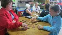Linda Taylor of Ropesville and her granddaughter, 11-year-old Hallie Cook of Bethune, Colo., challenge each other at checkers at the Castell General Store in Llano County.