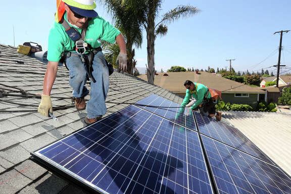 Workers from SolarCity install solar panels on a home in Camarillo (Ventura County).