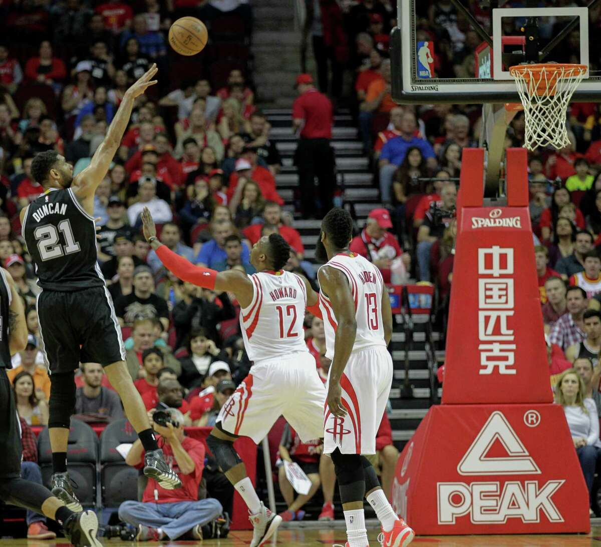 San Antonio Spurs forward Tim Duncan (21) shoots over Houston Rockets center Dwight Howard (12) as guard James Harden (13) looks on during the first half of an NBA basketball game Friday, April 10, 2015, in Houston.
