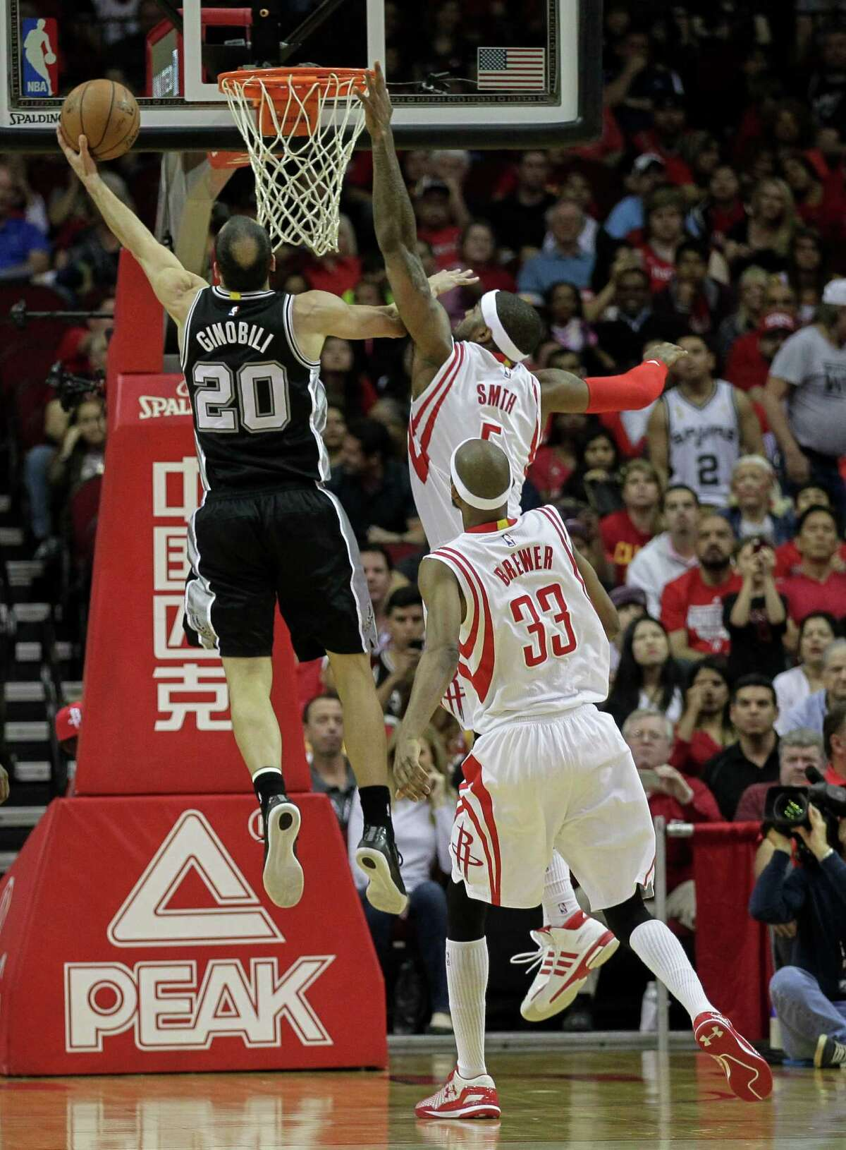 San Antonio Spurs guard Manu Ginobili (20) drives to the basket past Houston Rockets forward Josh Smith (5) and guard Corey Brewer (33) during the first half of an NBA basketball game Friday, April 10, 2015, in Houston.