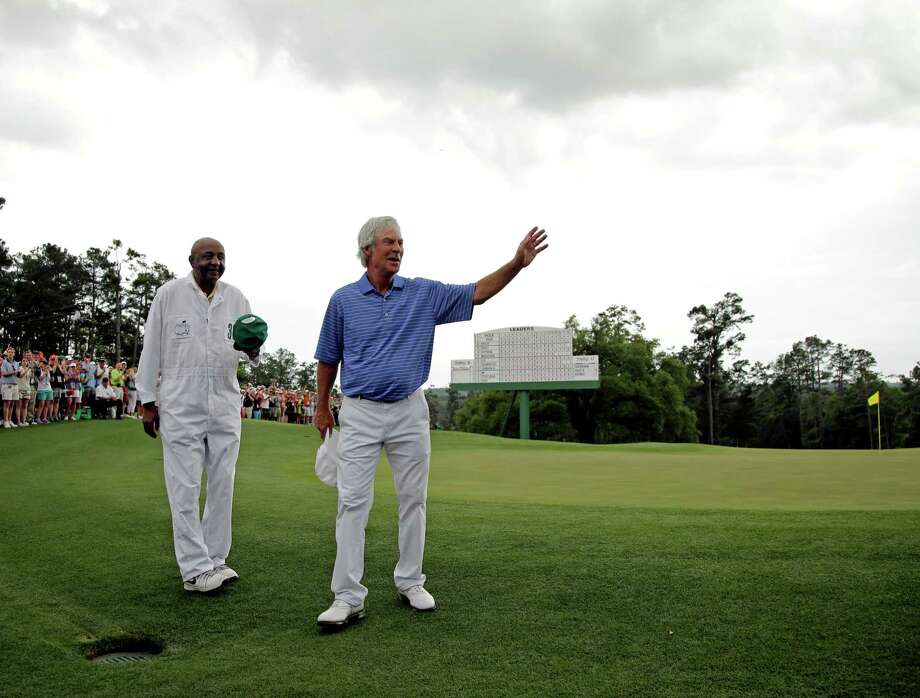 With longtime caddie Carl Jackson at his side, two-time Masters champion Ben Crenshaw, right, gives the gallery a final wave Friday following his last competitive round at Augusta National. Photo: Matt Slocum, STF / AP
