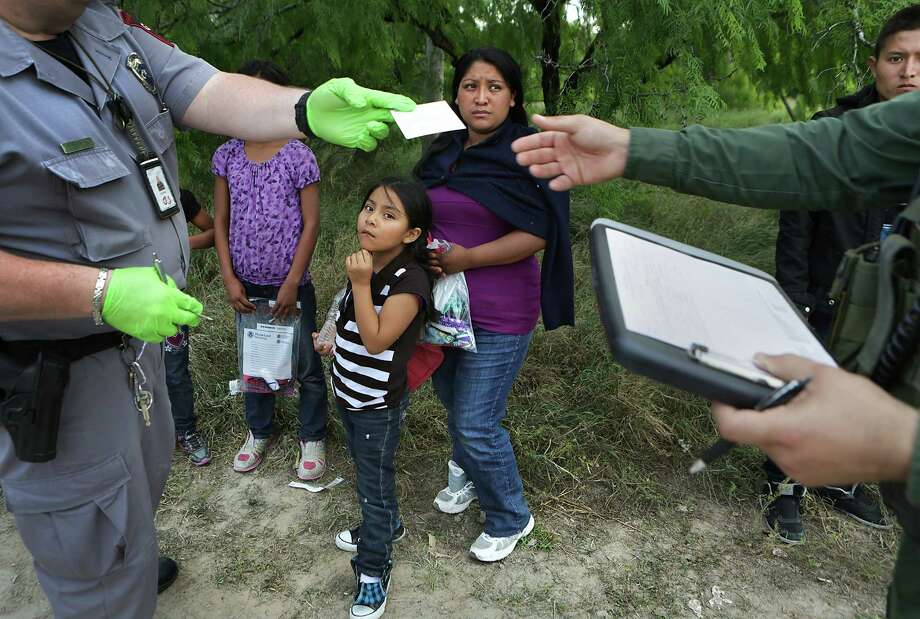 Guatemalan immigrants encountered by Border Patrol agents and Texas game wardens, wait as paper work is filled out.  Central America immigrants continue to cross the Rio Grande in search of a life away from the violence and poverty. Photo: Bob Owen, Staff / © 2015 San Antonio Express-News