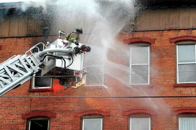 Firefighters battle a 5-alarm fire that involved two buildings at 4th and Washington streets on Friday, April 10, 2015, in Troy, N.Y. (Cindy Schultz / Times Union) Photo: Cindy Schultz / 00031404A