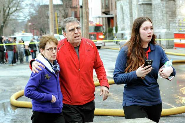 George Regan, who owns 231 and 233 4th St., walks with City Councilwoman Lynn Kopka, left, and his daughter Lilly Regan at the scene of the 5-alarm fire on Friday, April 10, 2015, in Troy, N.Y. Lilly Regan lived in one of the apartments that was ruined in the fire. (Cindy Schultz / Times Union) Photo: Cindy Schultz / 00031404A