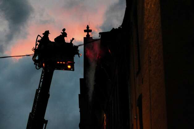 Firefighters at the scene of a 5-alarm fire that involved two buildings at 4th and Washington streets on Friday, April 10, 2015, in Troy, N.Y. (Cindy Schultz / Times Union) Photo: Cindy Schultz / 00031404A