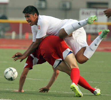 Hidalgo's Juan Mireles (4) falls over Fredericksburg's Ian Kendrick (5) during a battle for the ball in a 4A boys regional semifinal game at Richard Thompson Stadium April 10, 2015 in Mission. Photo: Joel Martinez, THE MONITOR / THE MONITOR / THE MONITOR