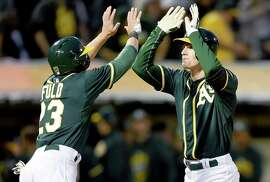 OAKLAND, CA - APRIL 10: Mark Canha #20 of the Oakland Athletics is congratulated by Sam Fuld #23 after Canha hit a two-run homer against the Seattle Mariners in the bottom of the third inning at O.co Coliseum on April 10, 2015 in Oakland, California. (Photo by Thearon W. Henderson/Getty Images)