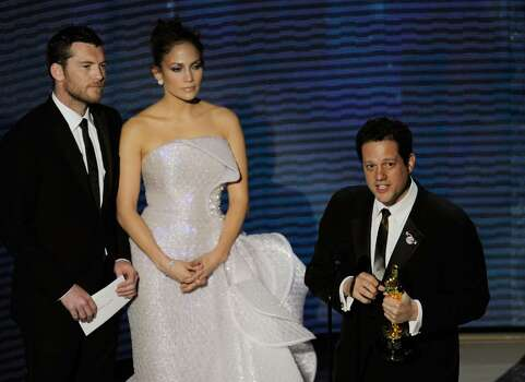 """HOLLYWOOD - MARCH 07:  Composer Michael Giacchino accepts Best Original Score award for """"Up"""" onstage from presenters Sam Worthington and Jennifer Lopez during the 82nd Annual Academy Awards held at Kodak Theatre on March 7, 2010 in Hollywood, California.  (Photo by Kevin Winter/Getty Images) *** Local Caption *** Michael Giacchino;Sam Worthington;Jennifer Lopez Photo: Kevin Winter, Getty Images / 2010 Getty Images"""