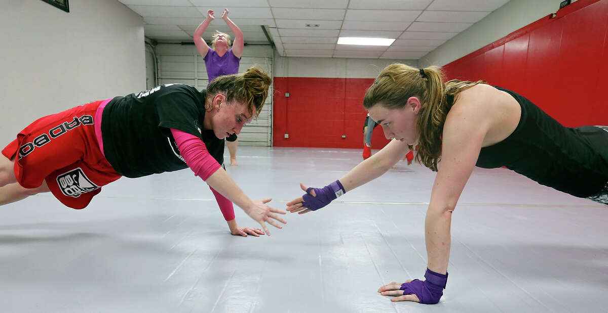 Laurie Ashby, 27, (left) and Summer Thunert, 27, do buddy pushups Monday April 6, 2015 during a Strike Fit class at Battle Tactics Academy.