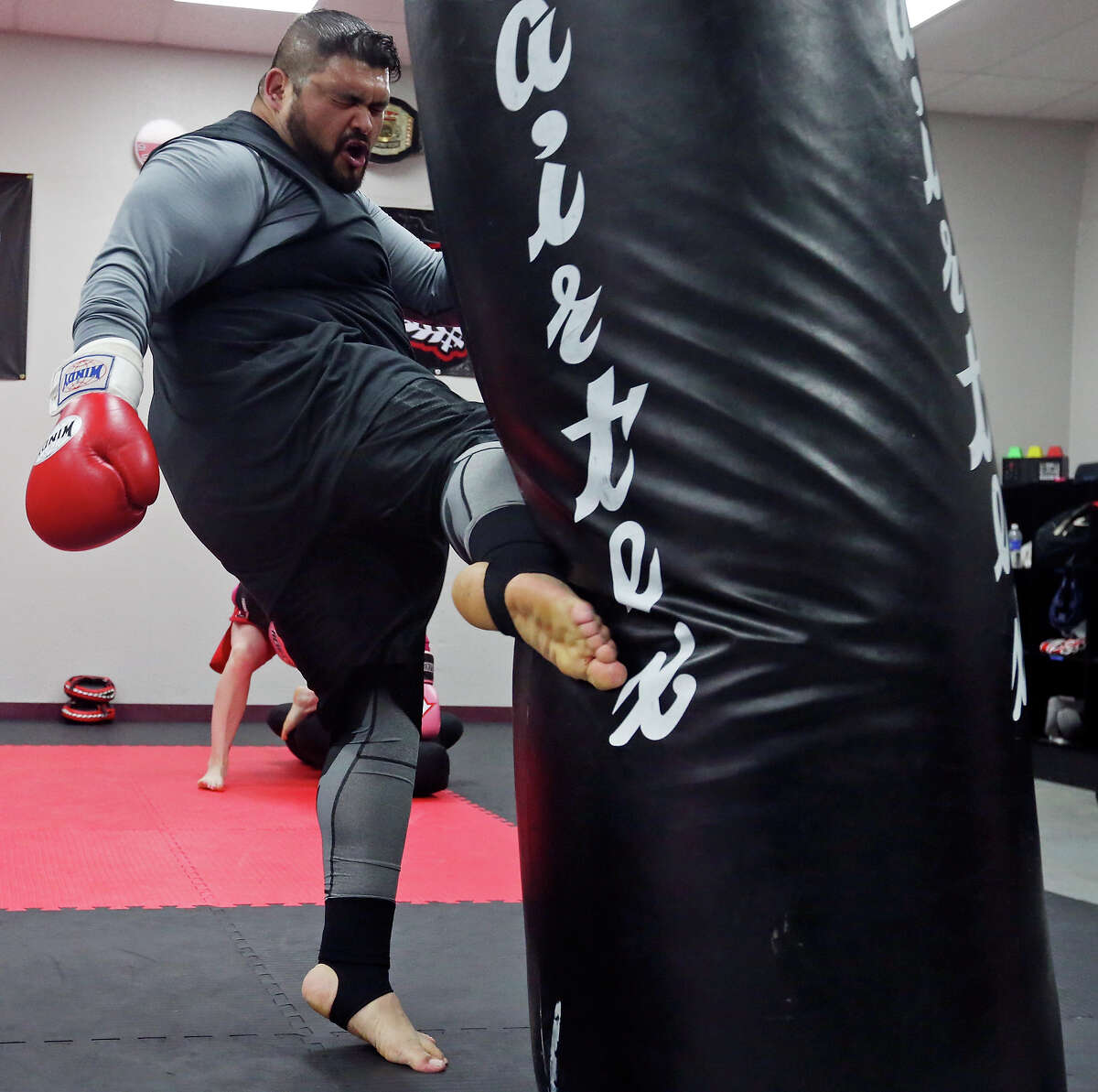 Robert Longoria, 31, kicks the heavy bag Monday April 6, 2015 during a Strike Fit class at Battle Tactics Academy.