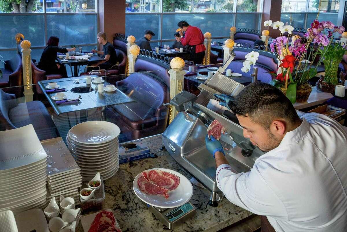 Ricardo Ramirez slices meat for the hot pot at Dragon Beaux in San Francisco.