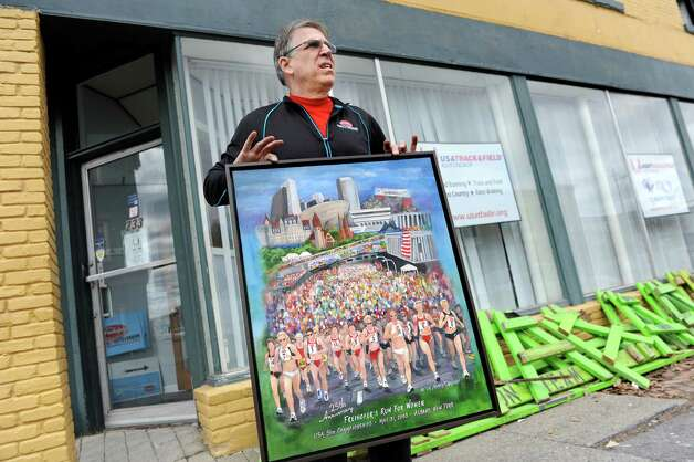George Regan, organizer of the Freihofer's Run for Women, holds a painting that was unharmed as he sifts through the office on Saturday, April 11, 2015, in Troy, N.Y. The painting by Nancy Chakrin commemorates the 25th anniversary of the annual run. Regan's three-story building at 231 and 233 4th St., which includes first floor offices and four apartments, was ruined in a fire on Friday. (Cindy Schultz / Times Union) Photo: Cindy Schultz