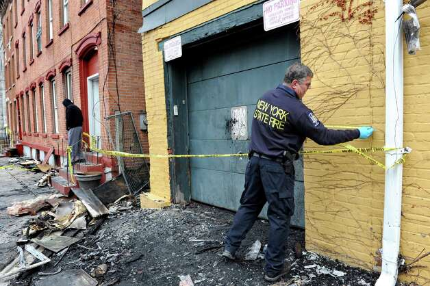 Investigator Rich Daus of the State Office of Fire Prevention, right, takes measurements of buildings on 4th and Washington streets on Saturday, April 11, 2015, in Troy, N.Y. The two buildings were heavily damaged by a fire on Friday. (Cindy Schultz / Times Union) Photo: Cindy Schultz