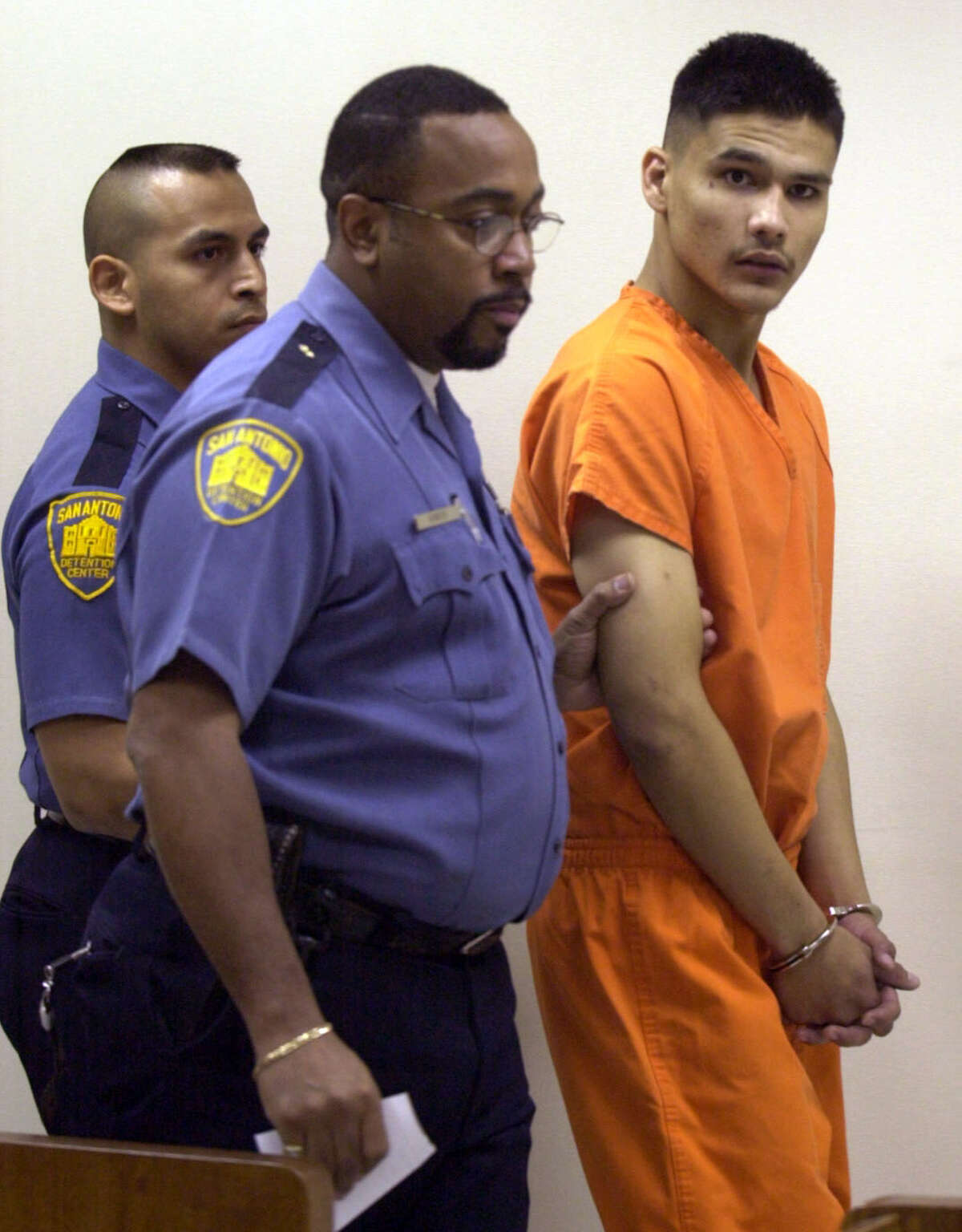 """Manuel Fernando Garza, 20, is escorted Sunday morning Feb. 4, 2001 into the magistrate's office to be charged with first degree murder in the shooting death of Officer John """"Rocky"""" Riojas."""