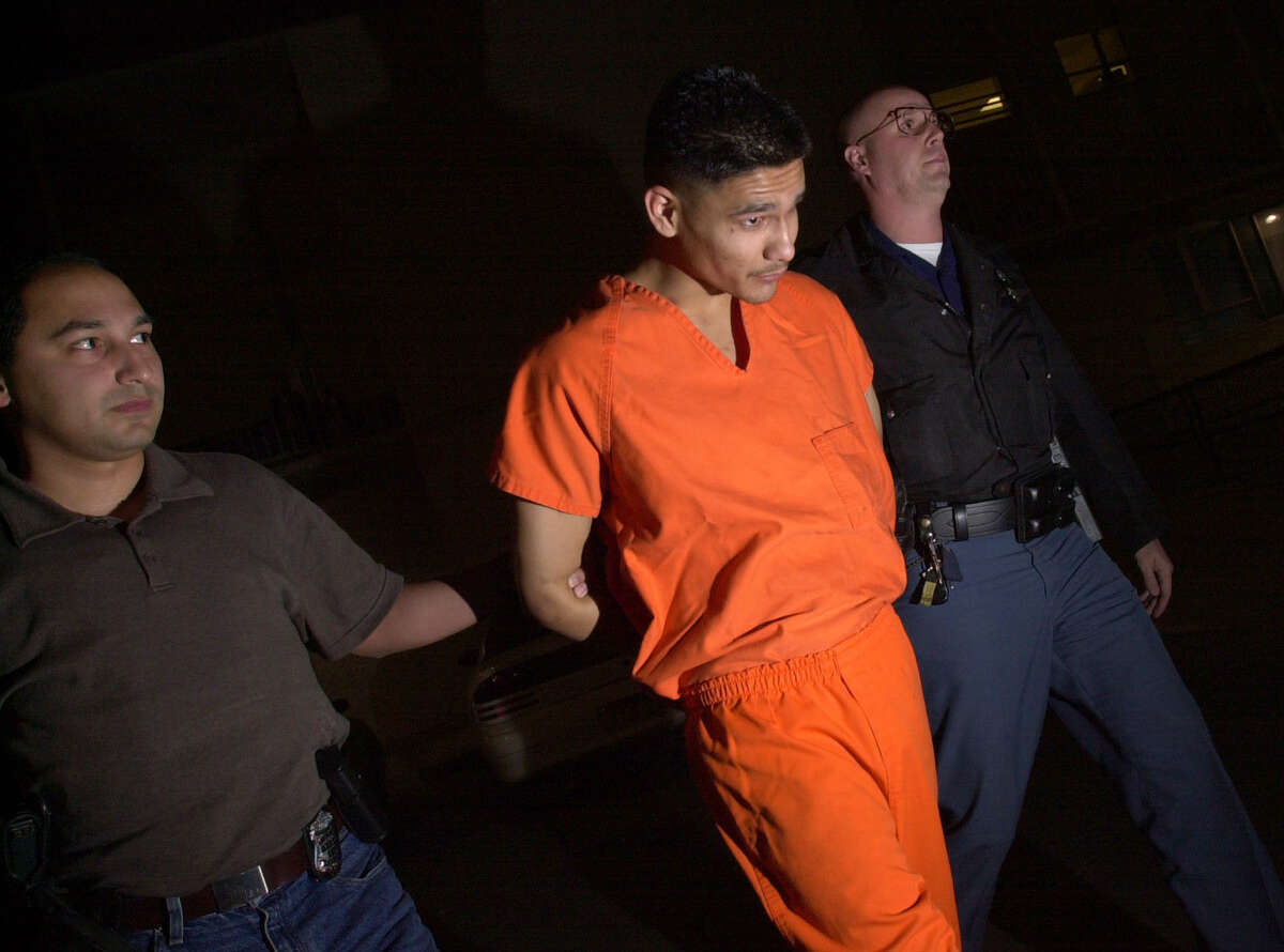 """STAFF PHOTO BY EDWARD A. ORNELAS --- Manuel Garza is escorted from the San Antonio Police Department early Sunday morning Jan 4, 2001 on his way to the magistrate's office. According to Police Sgt. Gabe Trevino Garza will be charged with capital murder in the shooting death of officer John """"Rocky"""" Riojas."""