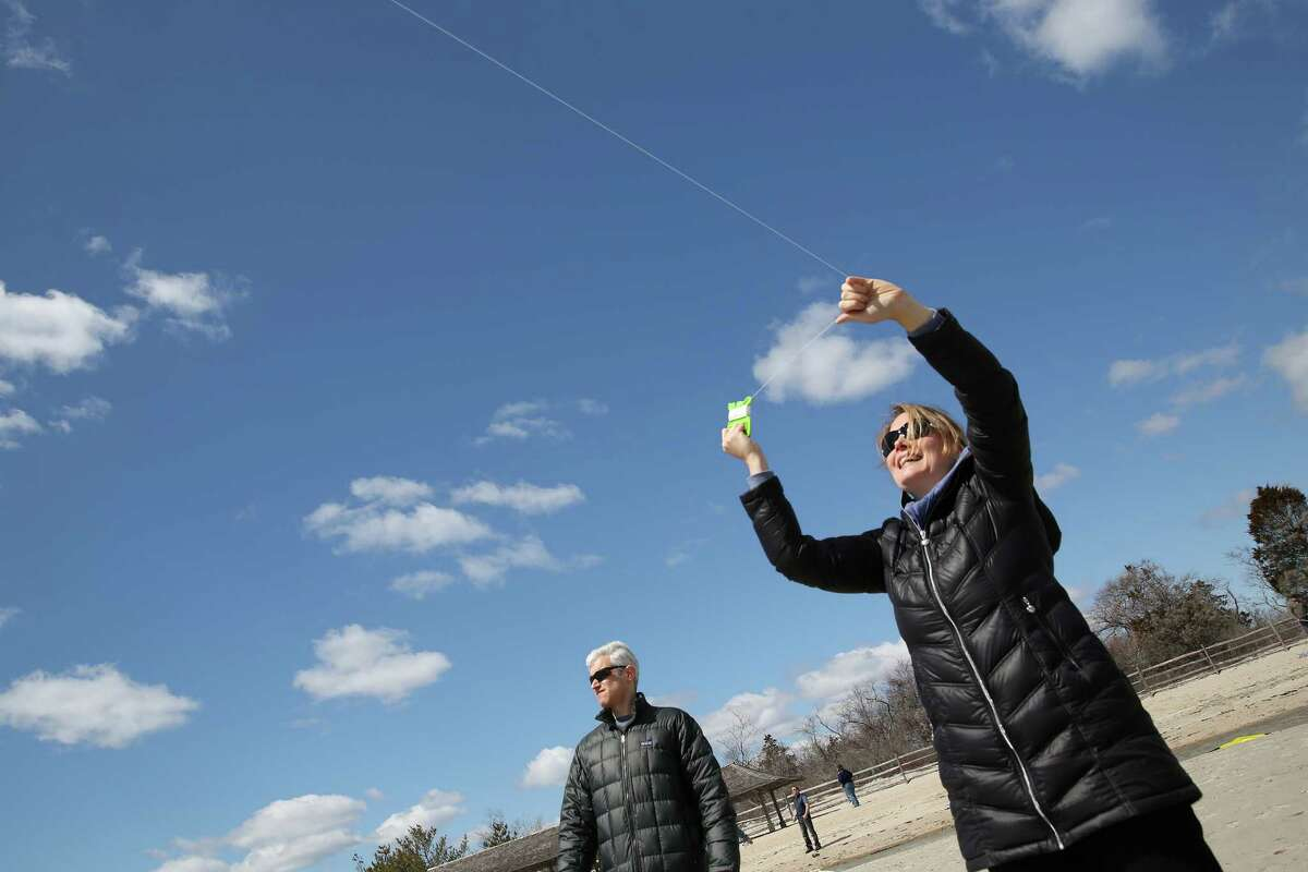 Christine Winston of Greenwich sails her kite as her husband Andrew looks on during Saturday afternoon annual Kite Flying Festival sponsored by Greenwich Department of Parks and Recreation. The event was held at Greenwich Point.