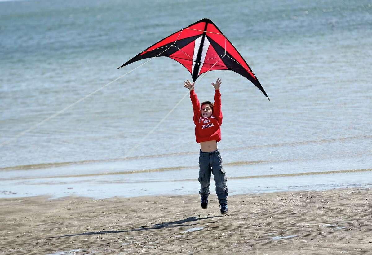 Santi Seitun age 6 of Riverside helps his father Francisco lift off their coloful kite during Saturday afternoon annual Kite Flying Festival sponsored by Greenwich Department of Parks and Recreation. The event was held at Greenwich Point.