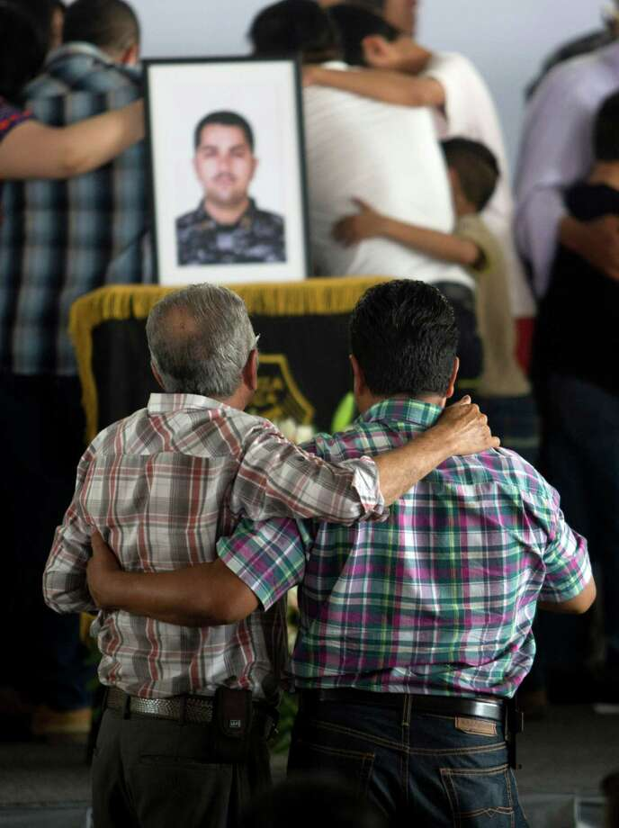 Mourners comfort each other during a ceremony to honor slain policemen in Tlaquepaque, Mexico. Photo: Refugio Ruiz /Associated Press / AP