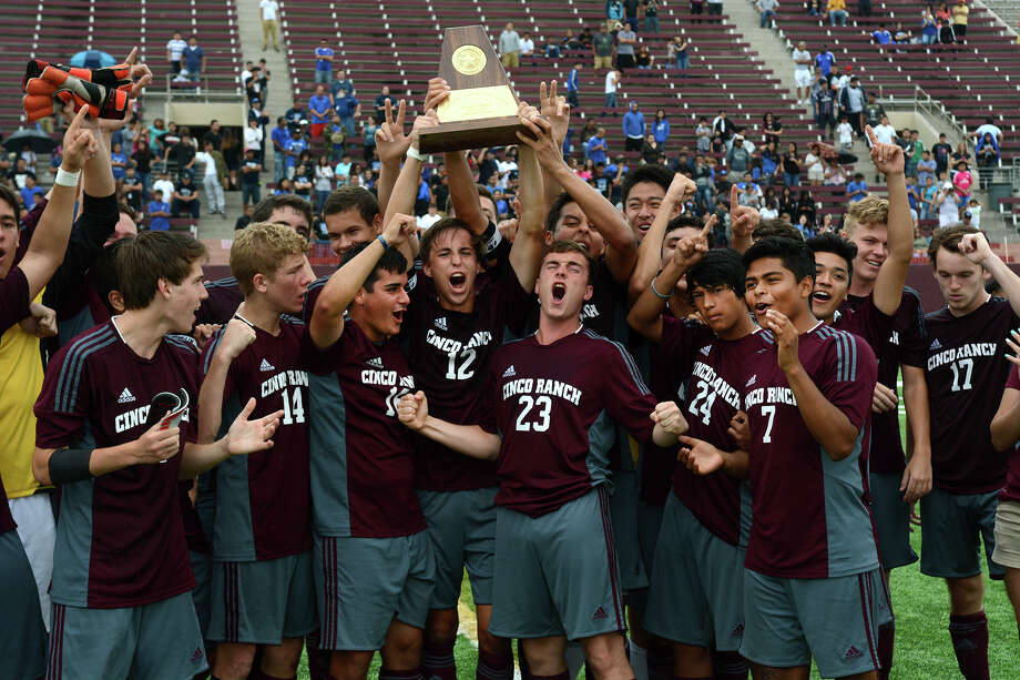 Cinco Ranch senior defender Chris Stamm hoists the trophy as he and his teammates celebrate their win over 2-1 Aldine and the trip to state it clinched. Photo: Jerry Baker, Freelance
